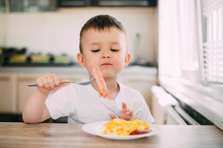 ein Kind in einem T-Shirt in der Küche isst eine Wurst und ein Omelett mit einer Gabel ist sehr lecker