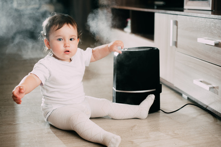 The baby looks at the humidifier. The concept of humidity in the home and health 스톡 콘텐츠