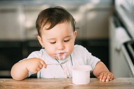 A small, cheerful, charming girl eats yogurt all smeared herself Stock fotó
