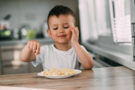 a child in the kitchen during the day eating pasta in a spiral in a white t-shirt at the table