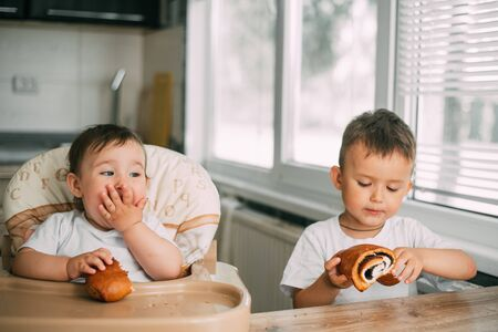 charming children in the kitchen in the afternoon eating buns with poppy seeds, boy and girl, family