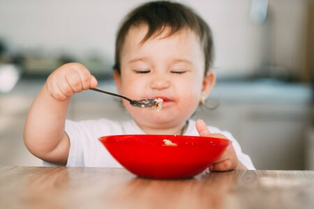 Funny little girl in the kitchen in the afternoon eating oatmeal porridge from a red plate all dirty Stock Photo