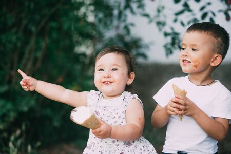 Brother and sister are very cute on the street in summer eating ice cream in the horn Banco de Imagens