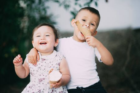 Kids eat ice cream in summer outside and cuddle Banco de Imagens