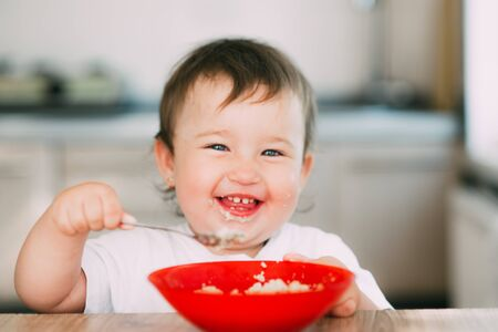 Funny little girl in the kitchen in the afternoon eating oatmeal porridge from a red plate all dirty