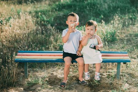 Brother and sister eating ice cream on the bench in the Playground
