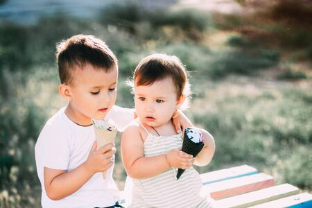 children, brother and sister on the bench eating ice cream is very fun and cute
