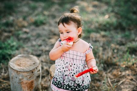 Charming girl year and a half, eating watermelon outdoors, in the village against the trees with a tail on his head Banco de Imagens