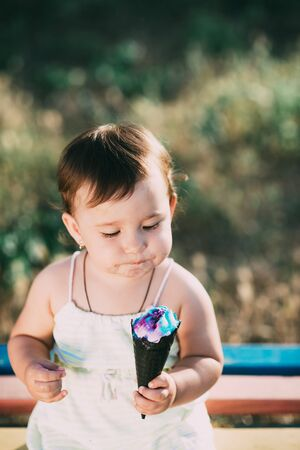 cute girl eating ice cream in a black horn of blue color, funny and beautiful Banco de Imagens