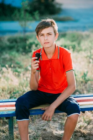 teen on a bench eating ice cream in a red t-shirt in the summer