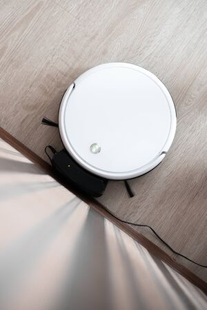 white robot vacuum cleaner in the interior on a light laminate is charging near the wall Banco de Imagens