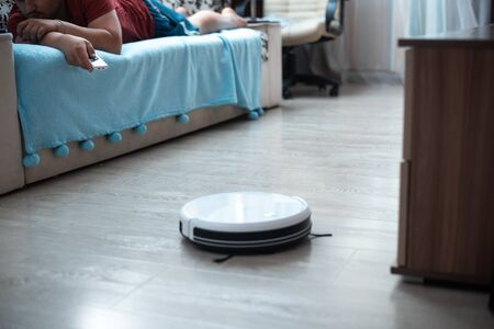 full man lying on the couch with remote control and controls the robot vacuum cleaner Archivio Fotografico