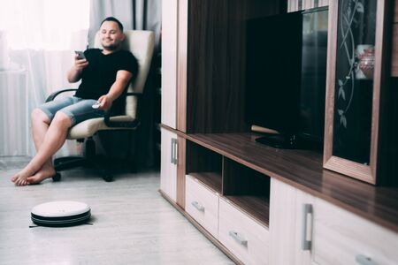 a man sitting on an office chair with a remote control and controls a robot vacuum cleaner white Banco de Imagens