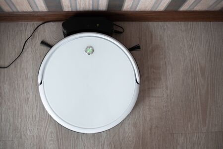 white robot vacuum cleaner in the interior on a light laminate is charging near the wall