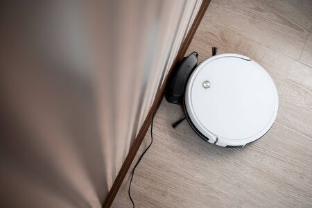 white robot vacuum cleaner in the interior on a light laminate is charging near the wall Stock fotó