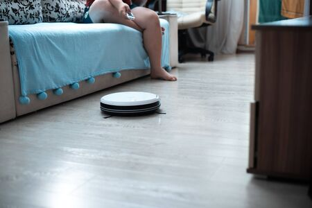 a fat man sitting on a couch with a remote and controls a white robot vacuum cleaner