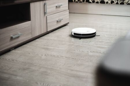white robot vacuum cleaner in the interior on a light laminate or parquet cleans