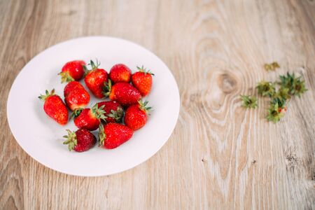 fresh strawberries in a bowl next to the tails Banco de Imagens