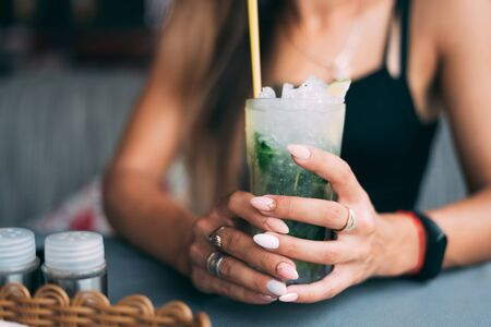 Beautiful summer girl in cafe with refreshing Mojito cocktail