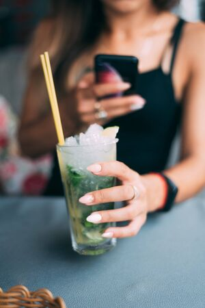 a girl in a cafe with a Mojito cocktail in the foreground in focus, taking pictures on a smartphone that is out of focus, posting on social networks Imagens