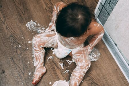 blue-eyed little girl sitting on the floor smears cream or cream all over her body very dirty, funny girl, makes a machete for the body