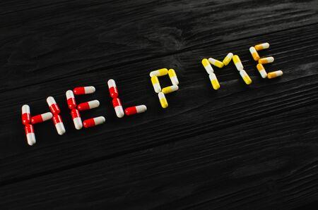 Word HELP made of pills on dark background.