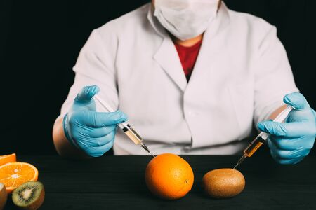 Injection of orange fruit. Isolated on white in the studio