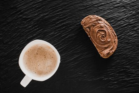 Coffee cappuccino or latte next to bread with chocolate on a black background
