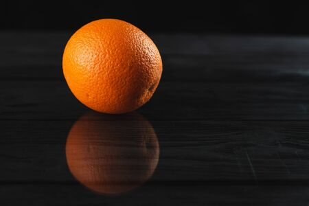 Fresh fruit oranges on black wooden background with reflection in the studio