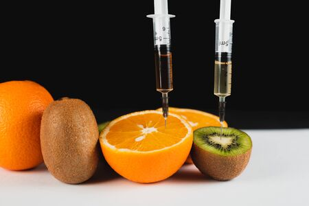Orange injections on a black background on a wooden table, GMOs and nitrates in the studio
