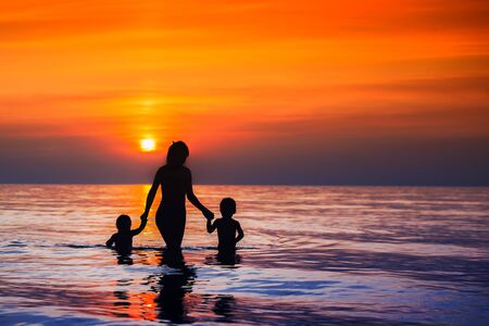Beautiful at sunset silhouettes of mothers with children walking from the sea to the shore, the concept of communication with children mom lonely mom loves her young children