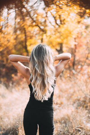 Attractive girl stands with her back to the camera on the background of autumn forest shows chic blonde hair 版權商用圖片