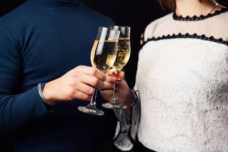 Girl and man on black background with champagne glasses, cute couple