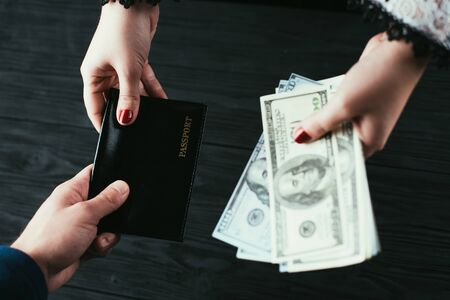 On a black wooden background, a top view of a hand handing over a passport and money loan approval concept. 版權商用圖片