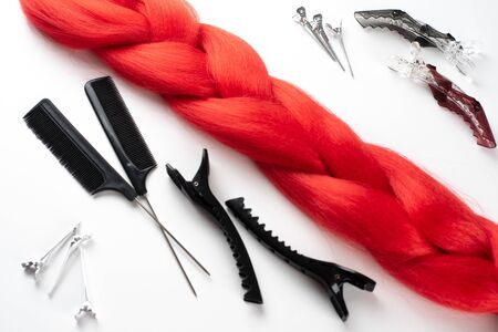 Kanekalon hair red on a white background top view close clips a comb and the spray 版權商用圖片