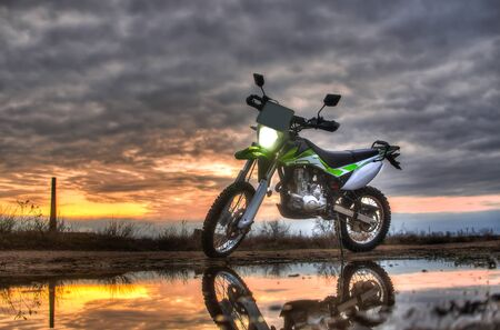 Beautiful green off-road motorcycle Enduro or cross, in reflection in a puddle on the background of sunset and sky