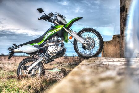 Beautiful green off-road motorcycle Enduro or cross, bounced on the plate, standing on the back wheel