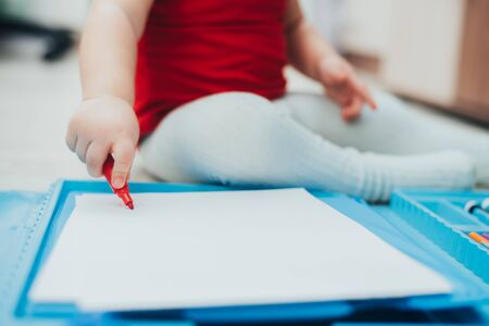 A little girl in a red t-shirt is drawing with a red marker on a blue easel cute