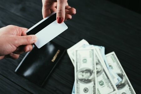 Male and female hands pass a credit card on the background of a black table where the money and passport lie, the concept of credit