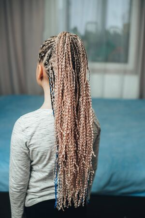 Little girl with Afro pigtails many pieces braided with artificial material cool