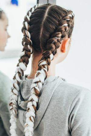 The girl with the pigtails, two braids with the addition of artificial material cool