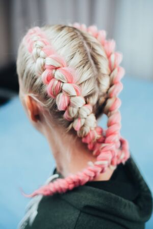 Girl with pigtails, two braids with the addition of artificial material in pink cool