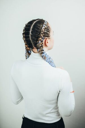 Girl with pigtails, two braids with the addition of artificial material in blue cute