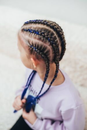 Braids with artificial material woven beautifully and fashionably, on a little girl cool 版權商用圖片