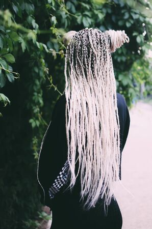 Beautiful Girl with pigtails is white as blonde on a background of green leaves beautiful and cute