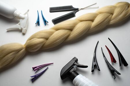 Kanekalon artificial hair of beige or cream color for braiding and Afro- hairstyles, lying on a white background next to accessories