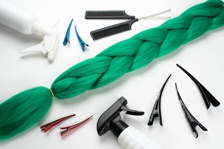 Kanekalon artificial hair of a dull green color for braiding braids, lying on a white background next to accessories