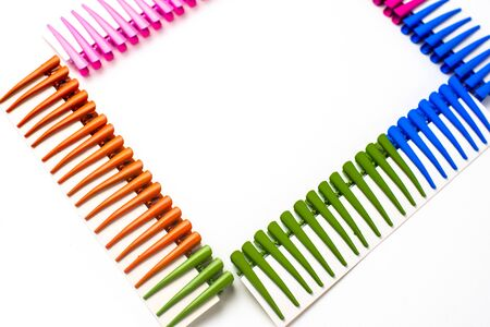 Frame of multi- colored hair clips on a white background, space for inscriptions, copy of the space white