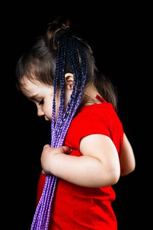 A little girl on a black background with Afro-pigtails, artificial plaited in elastic bands and put on cute Фото со стока