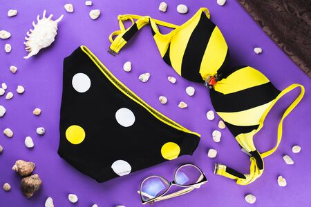 three-color swimsuit black white and yellow swimsuit with circles on a Purple background, next to sunglasses shells and stones cool 版權商用圖片